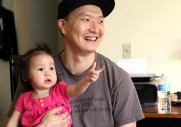 South Korean adoptee Adam Crapser poses with his 1-year-old daughter, Christal, in the family's living room in Vancouver, Wash., in 2015. Crapser, who was flown to the U.S. 37 years ago and adopted by an American couple at age 3, has been ordered deported back to South Korea.