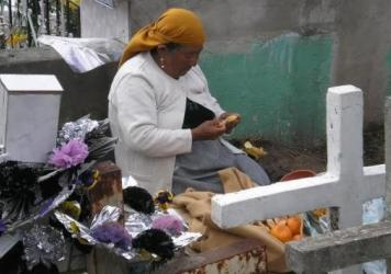 At Calderón cemetery near Quito, Ecuador, a woman shares a meal as a way to remember her loved ones.