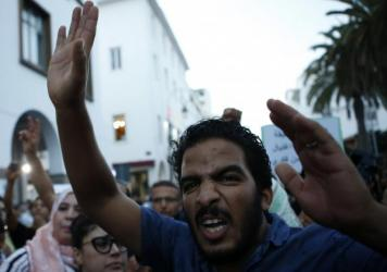 A Moroccan shouts as huge crowds in Rabat on Tuesday protest over a fishmonger's death in the northern city of al-Hoceima.