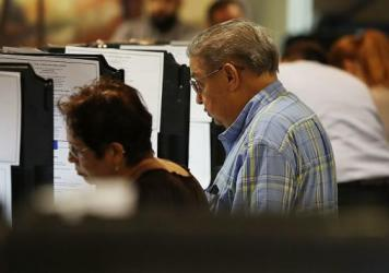 Voters cast their votes at an early voting center in Miami, Fla.
