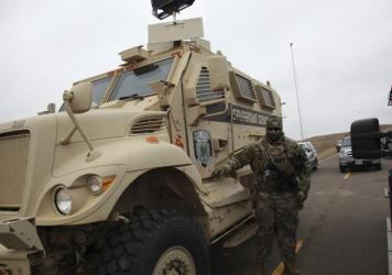 A member of the Stutsman County SWAT team who declined to give his name nor to be identifiable by badge stands guard by an armored personnel carrier equipped with an LRAD, or long range acoustic device, while deployed to watch protesters demonstrating ag