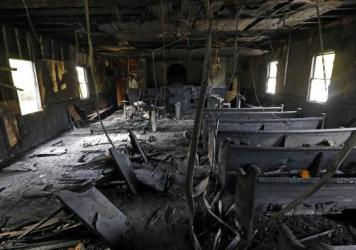 "Burned pews, musical instruments, Bibles and hymnals are part of the debris inside Hopewell M.B. Church in Greenville, Miss., shown Wednesday. The mayor is calling it a hate crime as arson investigators collect evidence at the black church, which was heavily damaged by fire and tagged with ""Vote Trump"" in silver spray paint."