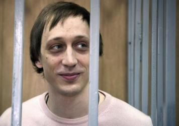 Pavel Dmitrichenko stands inside a barred enclosure in 2013 at a courtroom in Moscow.