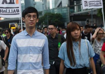 "Sixtus ""Baggio"" Leung (left) and Yau Wai-ching (right) of the Youngspirations party march during a protest in Hong Kong on Sunday. Hong Kong police used pepper spray to drive back hundreds of protesters angry at China's decision to intervene in a row ove"