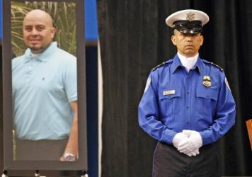 A Transportation Security Administration officer stands in front of a portrait of slain TSA officer Gerardo Hernandez during his public memorial in 2013 at the Los Angeles Sports Arena.