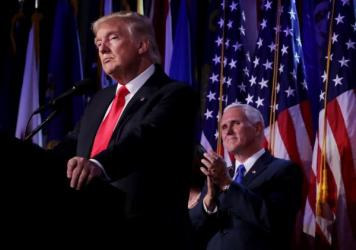 Republican president-elect Donald Trump delivers his acceptance speech as Vice president-elect Mike Pence looks on during his election night event at the New York Hilton Midtown in the early hours of Wednesday morning.