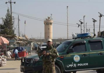 Afghan security personnel watch the area near the Bagram Air Field, after a suicide bomber killed four people inside the base.