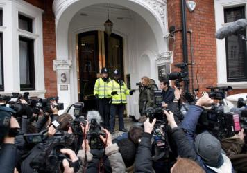 Police officers are surrounded by media as they stand outside the Ecuadorian Embassy in London on Monday, where WikiLeaks founder Julian Assange was set to be questioned over a rape allegation against him.