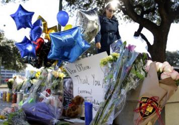 A woman leaves flowers at a makeshift memorial for slain San Antonio police Detective Benjamin Marconi on Monday. Marconi was fatally shot during a traffic stop Sunday near police headquarters.