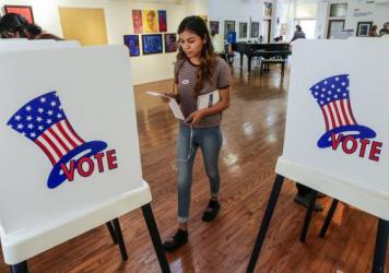 Maryjane Medina, 18, a first time voter, walks up to polling booth to cast her vote at a polling station set-up in Los Angeles, California.