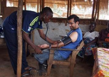 Dr. Raj Panjabi has his blood pressure checked by a Liberian community health worker.