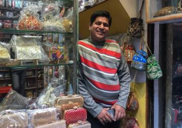 """In the Old City of New Delhi, Asim Husain stands in his shop, where he sells hand-stitched purses. He says sales normally conducted in cash are down nearly 90 percent and his attempts to go """"cashless"""" with credit cards or other e-wallet schemes have not"""