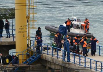 A search and rescue team attends to the crash site of a Russian Defense Ministry plane after the Tupolev Tu-154, with 92 people on board, fell off of radar over the Black Sea early Sunday.