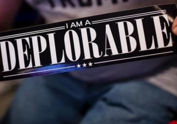 "A supporter of Republican presidential candidate Donald Trump shows a bumper sticker reading ""I am a Deplorable"" at Mohegan Sun Arena in Wilkes-Barre, Pennsylvania on October 10, 2016. The term references comments by Hillary Clinton that suggests Trump supporters are ""deplorables."""