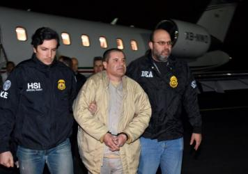 "Authorities escort Joaquin ""El Chapo"" Guzman to a waiting caravan of SUVs at Long Island MacArthur Airport on Thursday in Ronkonkoma, N.Y."