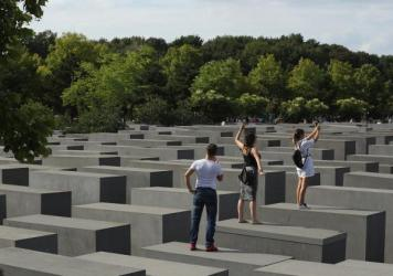 Visitors photograph each other while standing on concrete slabs at the Holocaust Memorial in Berlin on Aug. 13.