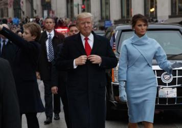 Barron Trump (left) waves as his mother and father walk the parade route after Donald Trump was sworn in as president Friday. A <em>Saturday Night Live</em> writer's tweet that mocked the 10-year-old has resulted in her indefinite suspension.