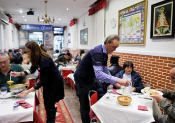 Volunteers serve free dinner to homeless people at Robin Hood restaurant in Madrid.