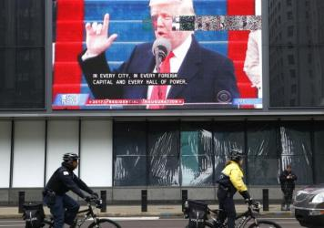 "Chicago police officials ride bikes by a broadcast of President Trump's inaugural address on Jan. 20. The president has threatened to ""send in the Feds"" to intervene in the city's law enforcement."