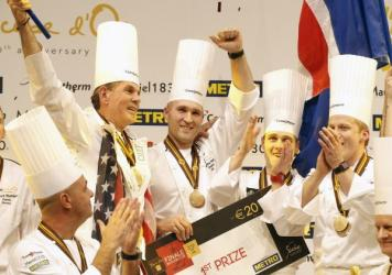 "U.S. chef Mathew Peters (center), celebrates on the podium with teammates after winning the ""Bocuse d'Or"" trophy, in Lyon."