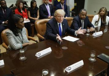 """President Trump, flanked by Omarosa Manigault and House and Urban Development Secretary-nominee Ben Carson, holds an African-American History Month """"listening session"""" on Wednesday."""