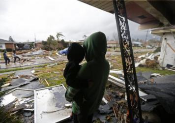 Eshon Trosclair holds her son Camron Chapital on Tuesday after a tornado tore through while they were inside their home in the eastern part of New Orleans. The National Weather Service says at least three confirmed tornadoes touched down, including one i