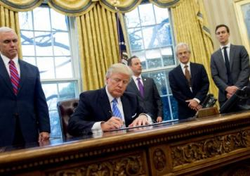 """President Trump signs an executive order alongside Vice President Pence administration officials. One of the documents Trump signed that day was a memorandum reinstating the """"Mexico City policy."""""""