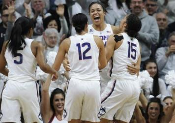 Connecticut's Napheesa Collier, (center) celebrates with teammates (from left) Crystal Dangerfield, Saniya Chong and Gabby Williams in Storrs, Conn., after beating South Carolina 66-55 — the Huskies' 100th win.