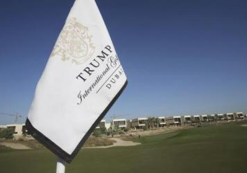 A flag flies on a green lined with villas at the Trump International Golf Club in Dubai, United Arab Emirates. The 18-hole golf course bearing Donald Trump's name exemplifies the questions surrounding his international business interests.
