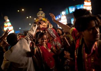 Wedding guests dance at a New Delhi celebration.