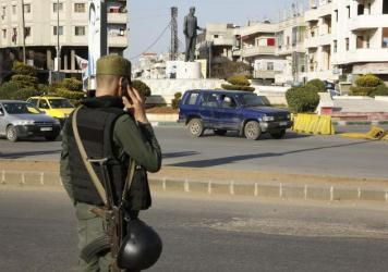 A member of the Syrian government forces mans a checkpoint in Homs, the country's third-largest city, on Saturday.