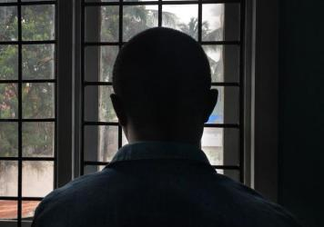 A gay man with HIV stands in a clinic in Dar es Salaam, Tanzania. He's been afraid to pick up his medicine because of the government's crackdown on the gay community.