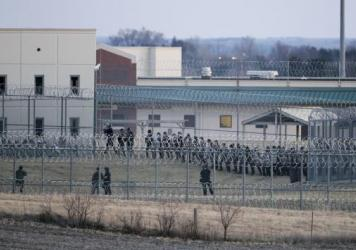 Security forces in riot gear  surround a courtyard behind razor wire at the Tecumseh State Correctional Institution in Tecumseh, Neb. Two inmates died during a disturbance that began Thursday afternoon.
