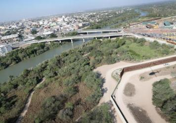 A U.S. Customs and Border Protection helicopter patrol flies over a border fence by a bridge between the United States and Mexico on Oct. 18, 2016 in Hidalgo, Texas.