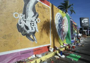 Artwork and signatures cover a fence around the Pulse nightclub, scene of a mass shooting, in Orlando, Fla. Noor Salman, widow of gunman Omar Mateen, is accused of aiding her husband's attack.