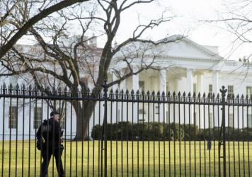 A member of the Secret Service walks the perimeter of the North Lawn of the White House in Washington, last March. On Friday night, an intruder entered the White House grounds while the President was home.