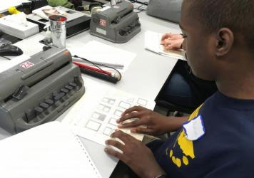 Marcus Johnson, a 12th-grader at the Tennessee School for the Blind, takes a timed test on interpreting charts and graphs, typing his answers into his Braille writer.