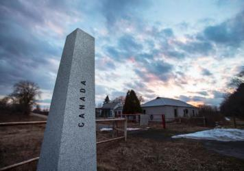 The sun sets behind an abandoned customs station on the US side of the Canada/U.S. border on Meridian Road in Champlain, N.Y., in Feb. 2017.