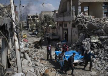 Residents carry the body of several people killed during fights between Iraq security forces and Islamic State on the western side of Mosul, Iraq, yesterday. Residents of the Iraqi city's neighborhood known as Mosul Jidideh at the scene say that scores o