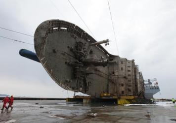 The ferry Sewol sits on a semi-submersible transport vessel during the salvage operation in waters off the island of Jindo on Sunday. On Tuesday, South Korean officials said remains believed to be from some of the missing victims were recovered by salvage workers.