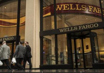 OSHA says a manager's report of suspected fraudulent activity was at least partly responsible for his firing. Here, pedestrians pass in front of a Wells Fargo bank branch in New York earlier this year.
