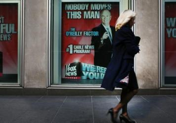 An ad for Bill O'Reilly's top-rated Fox News show stares back at passersby outside the News Corp. headquarters in New York City earlier this month. O'Reilly is stepping away from the show for a vacation as controversy continues to mount around sexual har