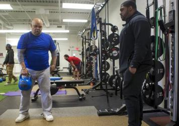 After a couple of stints behind bars, Angel LaCourt (right) is now a trainer at InnerCity Weightlifting in Boston. Here he works with Bill Gramby, who recently had a stroke and is working out to build strength and stamina.