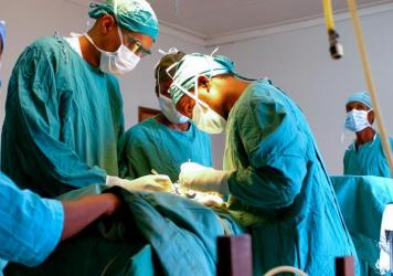 Dr. Dilan Ellegala, left, supervises Dr. Emmanuel Nuwas of Tanzania as he inserts a shunt in a baby with hydrocephalus. Ellegala has played a key role in training local doctors, as described in the new book <em>A Surgeon in the Village. </em>Early on, he trained a hospital staffer who wasn't a doctor to do brain surgery.