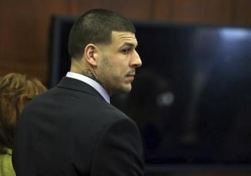 Aaron Hernandez stands at the defense table Thursday. On Friday, the former New England Patriots tight end was found not guilty of two counts of murder in a 2012 drive-by shooting. Hernandez is still serving a life sentence for a previous murder conviction.