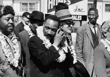 Martin Luther King, Jr. listening to a transistor radio in the front line of the third march from Selma to Montgomery, Alabama, to campaign for proper registration of black voters, March 23, 1965. Ralph Abernathy (second from left), Ralph Bunche (third f
