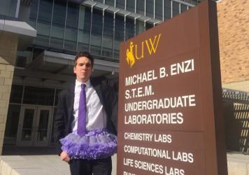 University of Wyoming student Tyler Wolfgang poses in front of the university building that bears Sen. Mike Enzi's name.