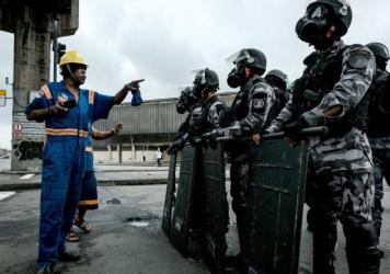A protester harangues a line of military police in riot gear in front of a Rio de Janeiro bus terminal during the nationwide strike Friday.