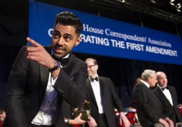 The Daily Show correspondent Hasan Minhaj stands at the head table during the White House Correspondents' Association Dinner in Washington on Saturday.