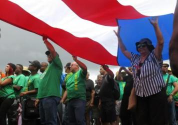 People carry a large Puerto Rican flag as they protest looming austerity measures amid an economic crisis in San Juan, Puerto Rico on Monday. The May Day demonstrations come as the island faces a Monday deadline for reaching a deal on debt payments, or entering bankruptcy-like proceedings.